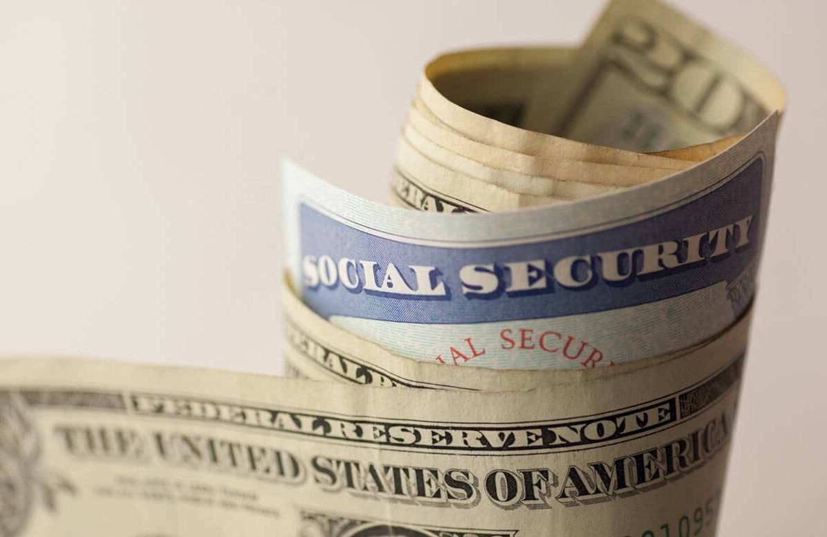 Social Security card wrapped in money