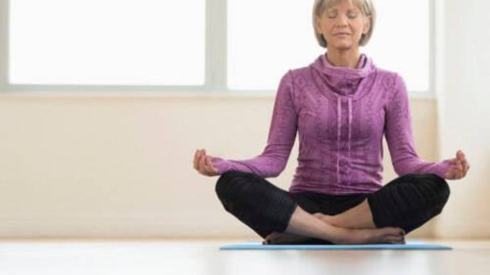 Mature Woman With Eyes Closed Sitting In Lotus Position