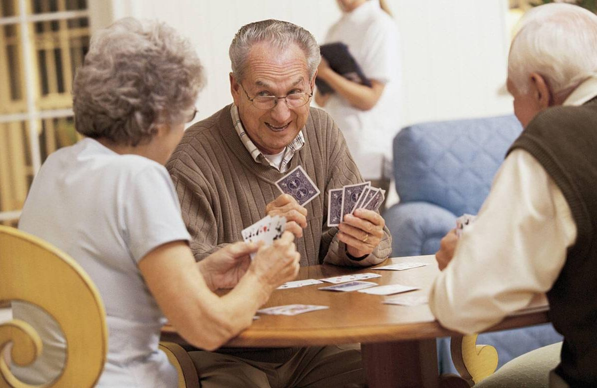 Group of mature adults playing card game