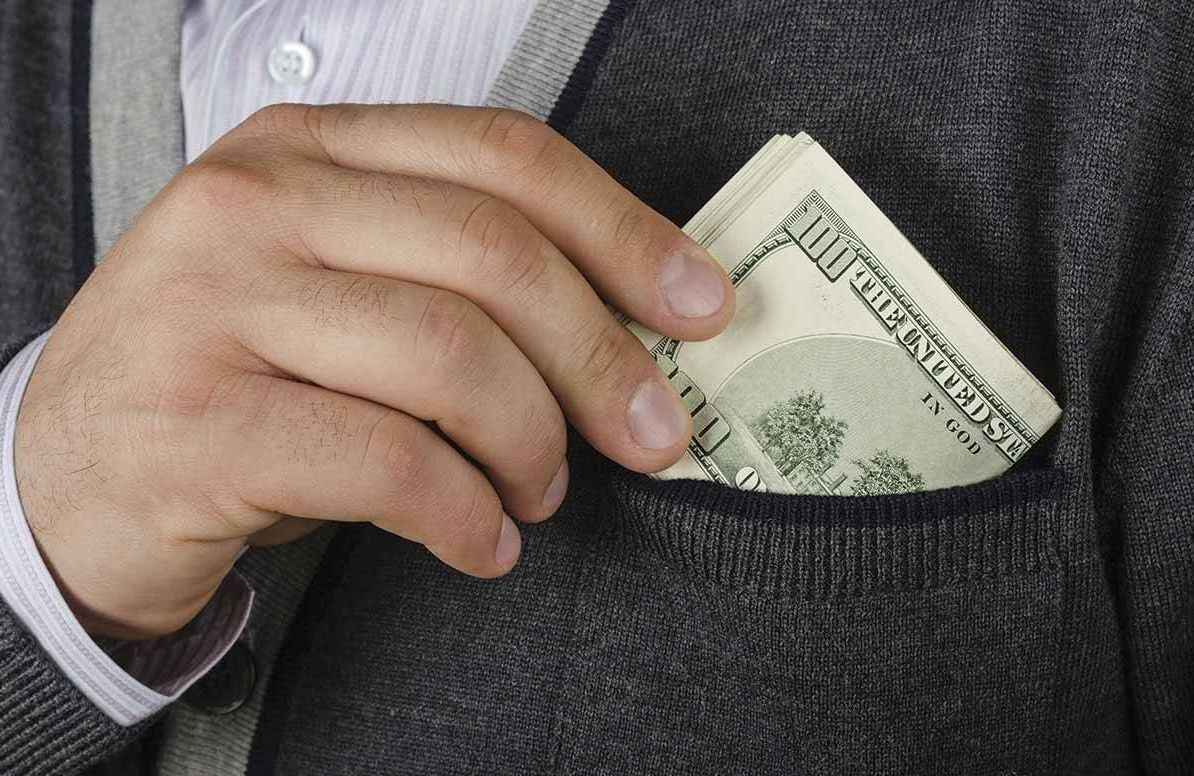 Man putting money in his sweater pocket
