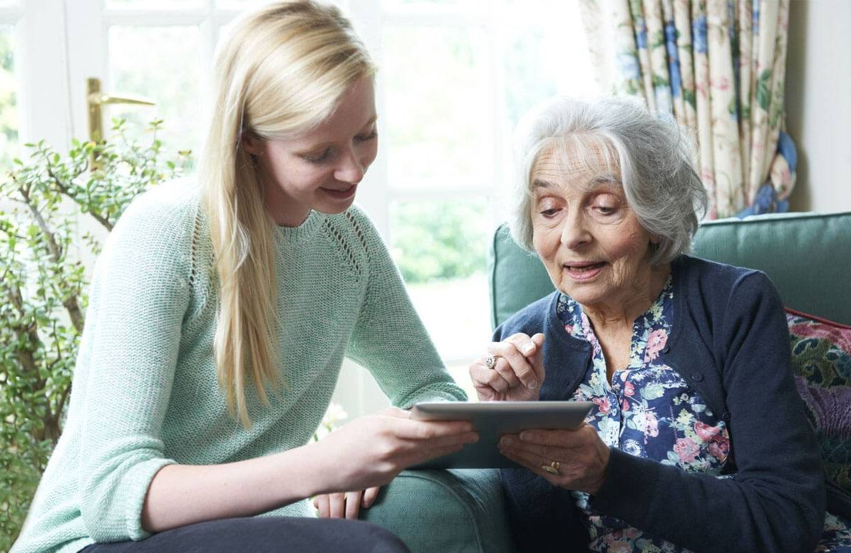 Teenager teaching a senior how to use technology