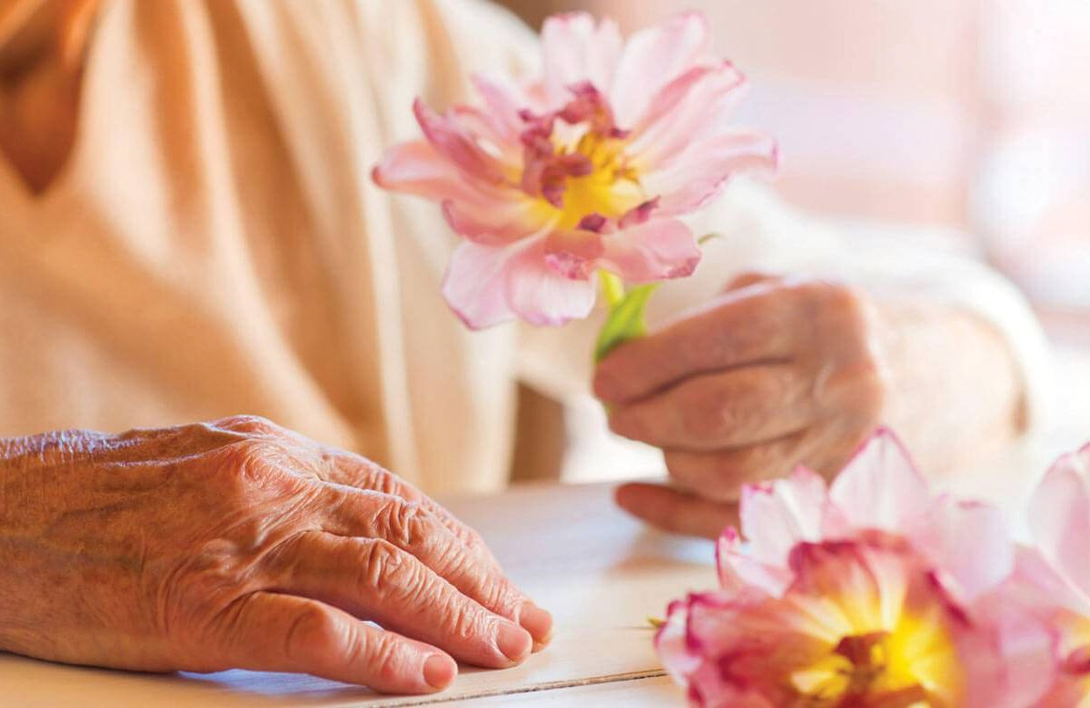Older woman holding a flower