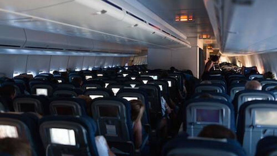 Cabin of modern airplane with passengers and seat monitors being on. Comfortable and fast traveling by air