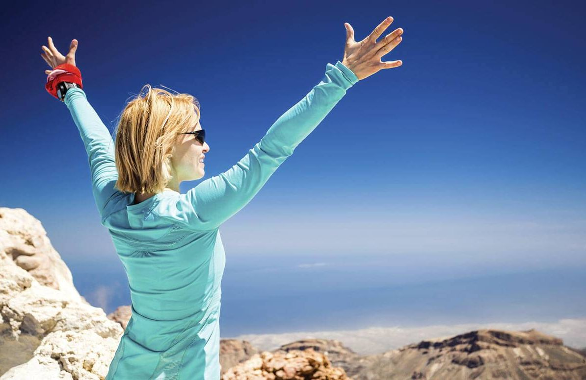 Woman celebrating on top of mountain