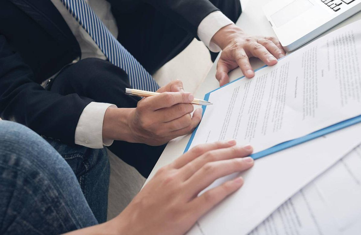 Two people reviewing and signing paperwork