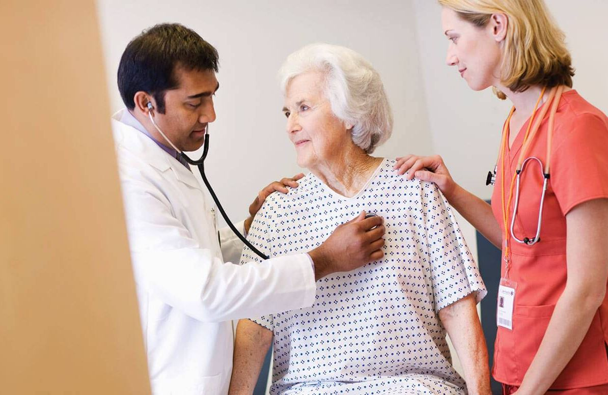 Older patient with doctor and nurse