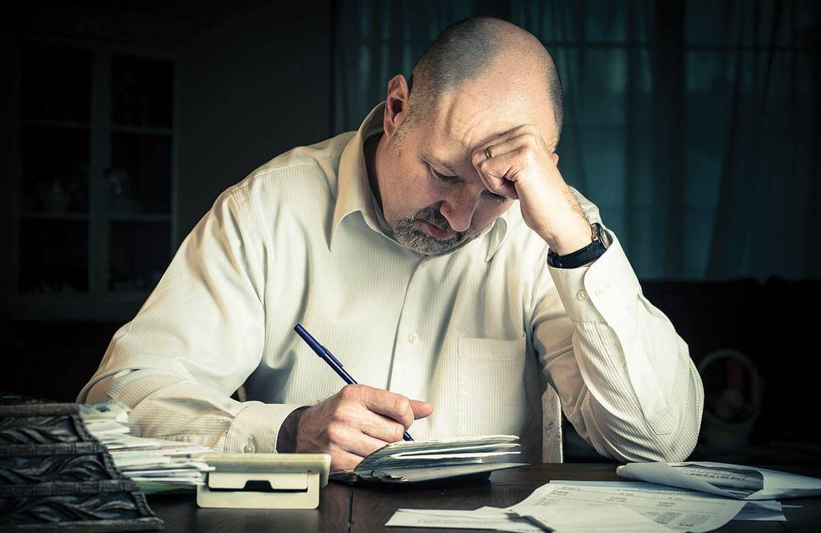 Stressed man reviewing finances