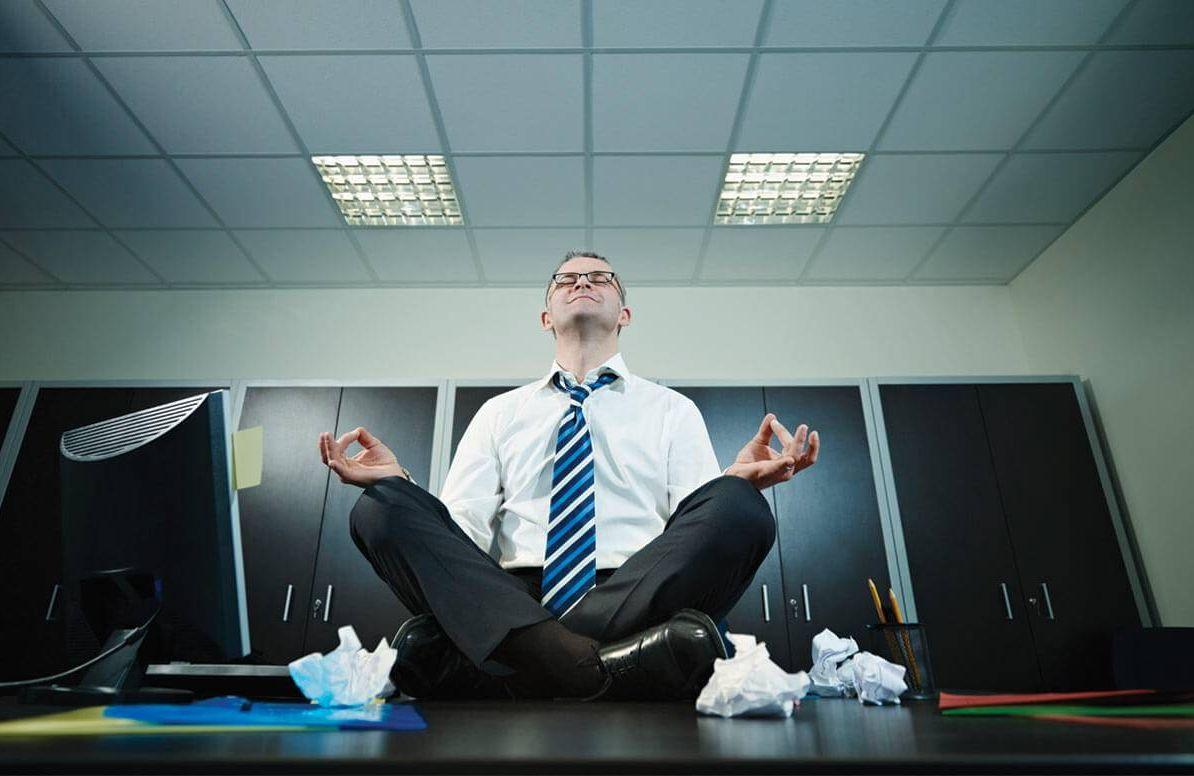 Man meditating on his desk