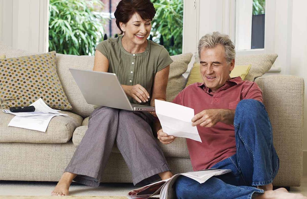 Middle Aged Couple With Bill And Laptop At Home