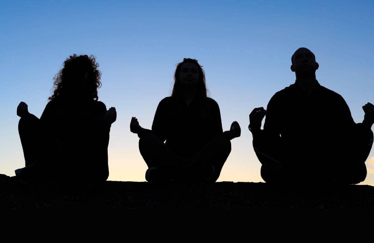 Silhouette of people meditating