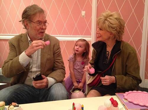 Lesley and her husband having a tea party with their granddaughter