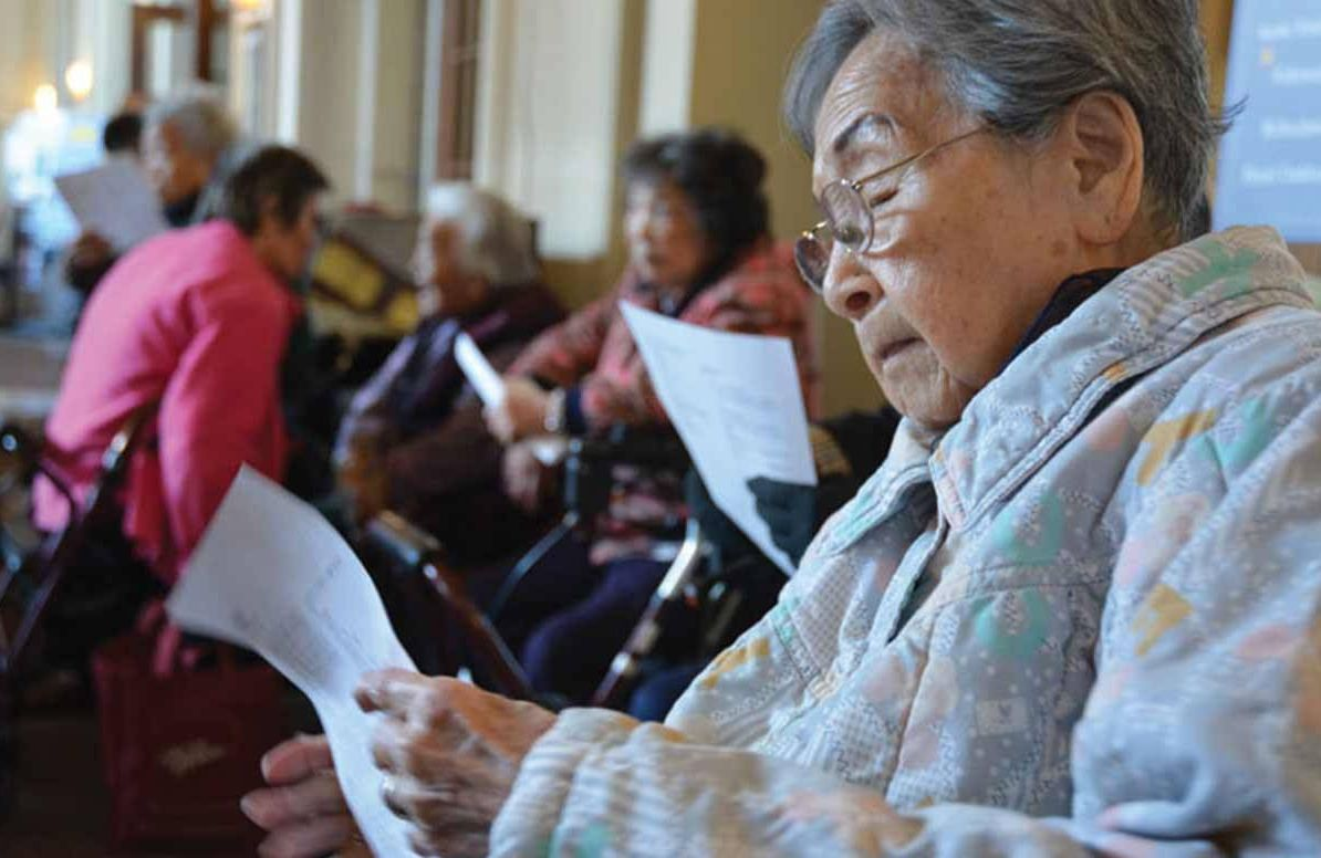 Kan-Lin Chu reads a handout on improving your memory in the lobby of the Hotel Oakland, a low-income senior housing facility in downtown Oakland, California.