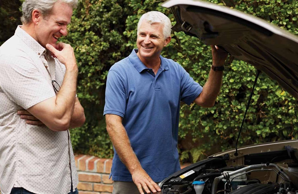 Men looking under hood of car