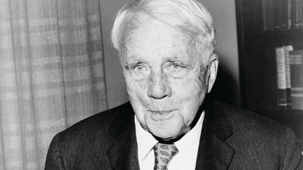 Robert_Frost, 1959, poses with his birthday cake on his 85th birthday at the Waldorf-Astoria hotel in New York City.