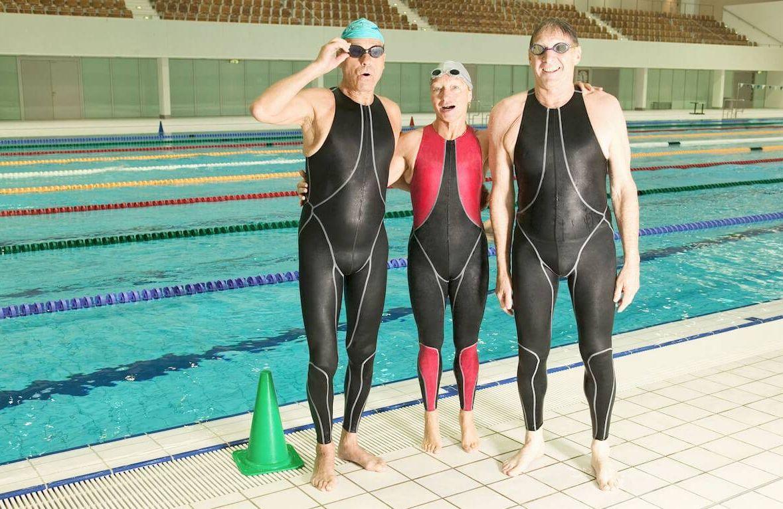 Three senior people wearing wetsuits at poolside