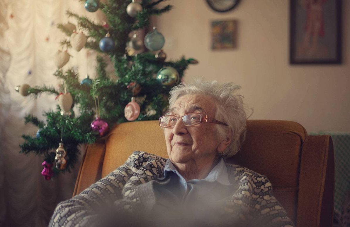 elderly woman sitting near a Christmas tree