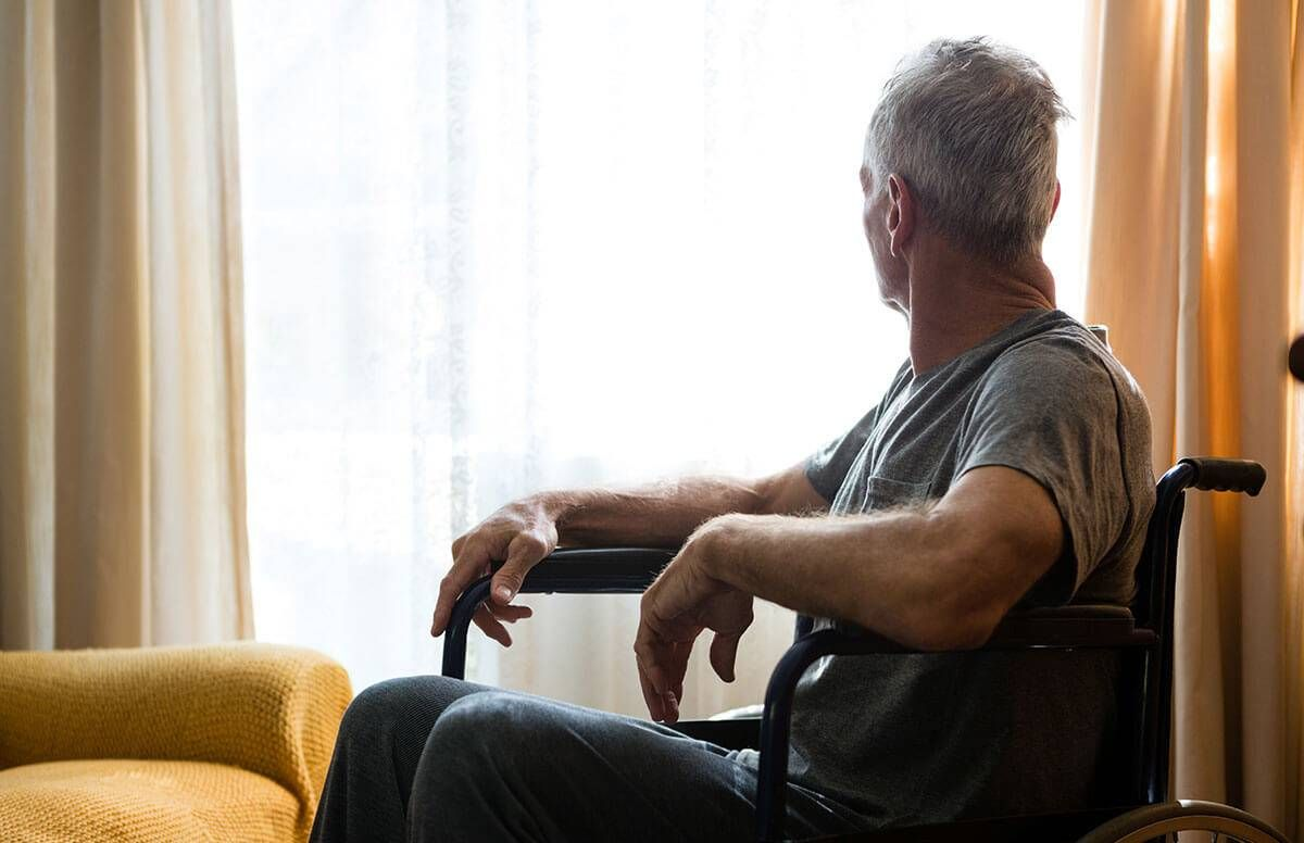 man sitting in wheel chair, looking out a window