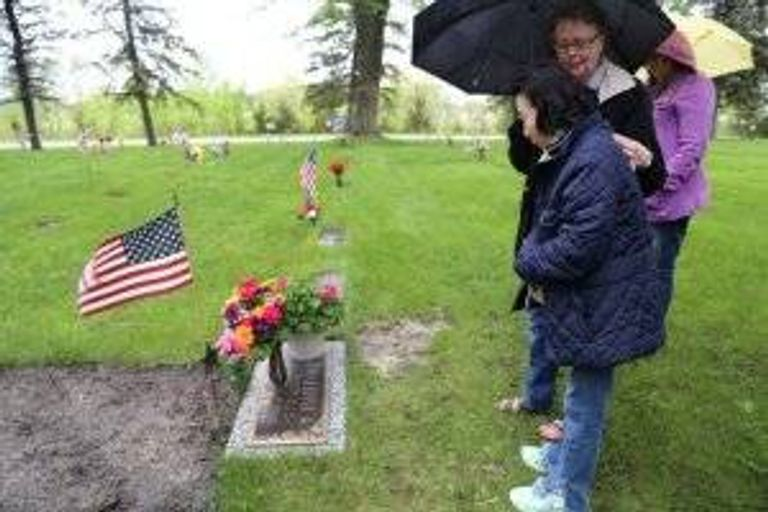 Sook-nyeon Kim pays her respects to her son's adoptive father, at his gravesite in Willmar, Minnesota.