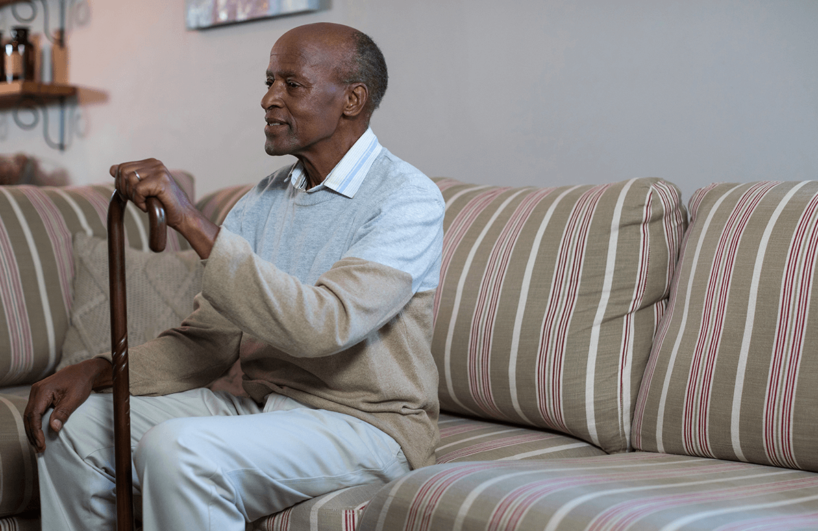 elderly African American man sitting on his couch at home, with a cane