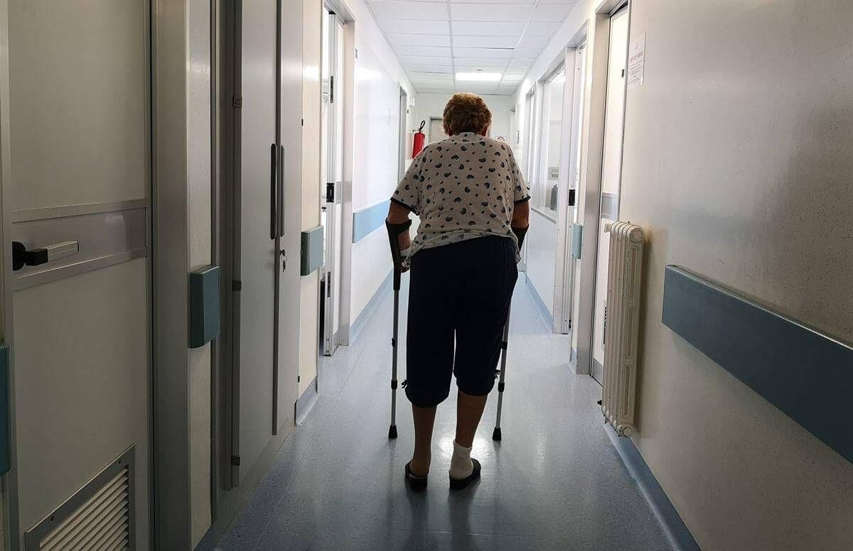 woman using a walker while walking down a hospital hallway