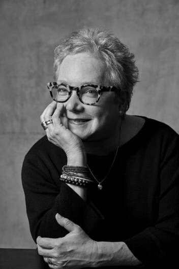 black and white headshot of woman with glasses and short hair leaning on a table with hand on chin