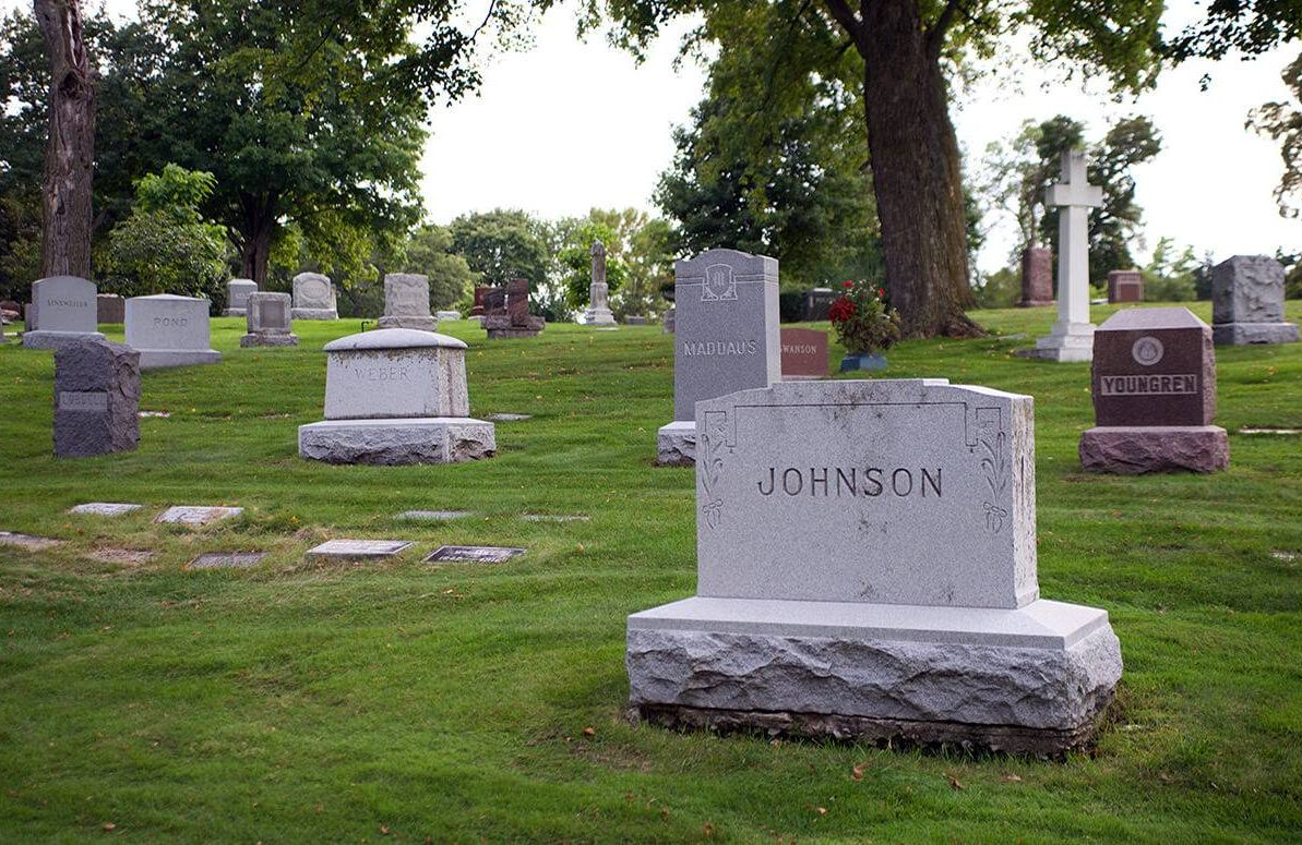 """gravestones in a cemetery with one reading """"Johnson"""" in the foreground"""