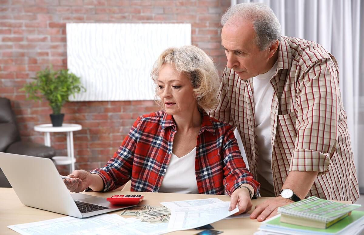 man and woman look at laptop together with papers, money, and calculator in front of them