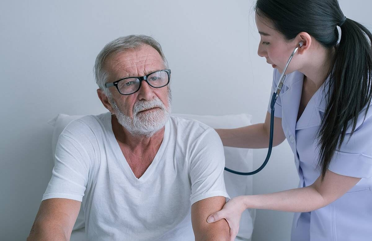 older man is examined by medical professional with a stethoscope