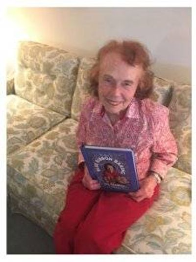 Marjorie Johnson sitting on her couch, holding a copy of her book