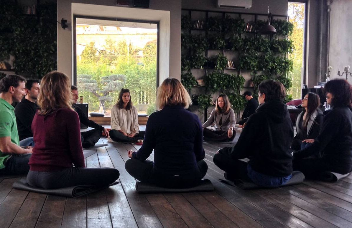 A group of adults sitting in a circle, meditating