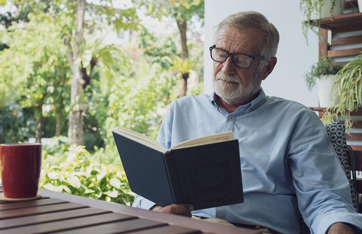 Older man reading outside