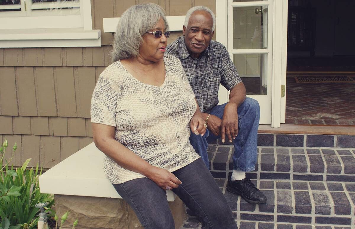 retired couple sitting on thier front stoop