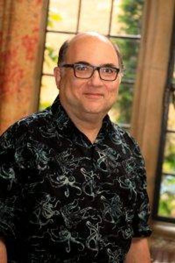 storyteller josh kornbluth in a printed shirt wearing glasses