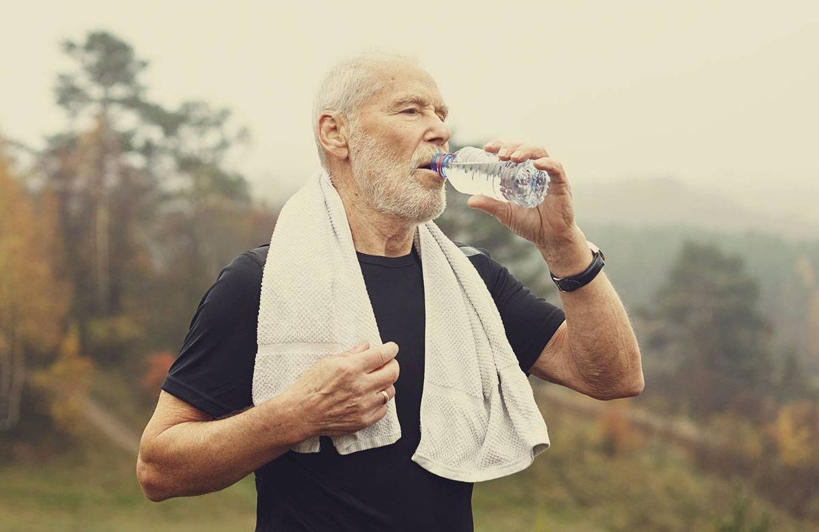 An older man stops to catch his breath and drunk water during an outdoor workout