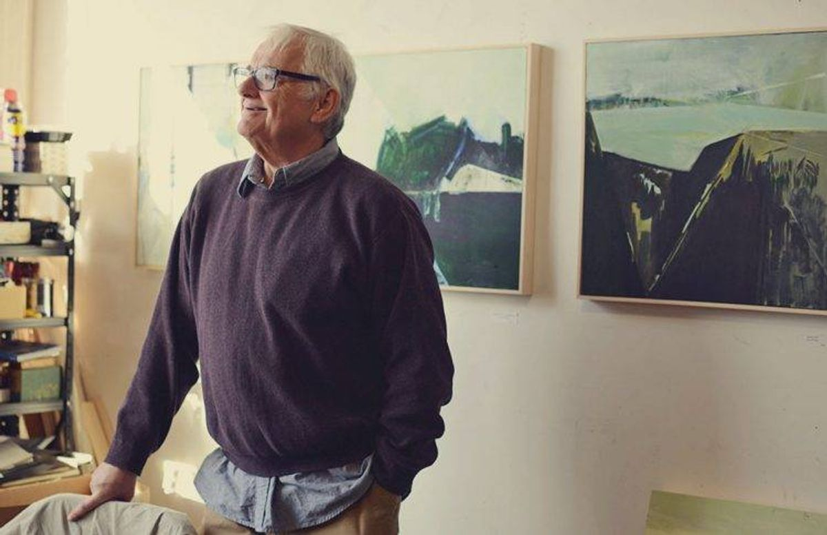 artist James Wrayge stands next to several of his paintings in his Minneapolis studio