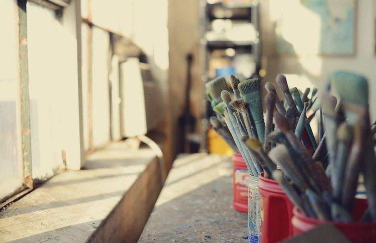 used paintbrushes sit next to a window in James Wrayge's Minneapolis studio
