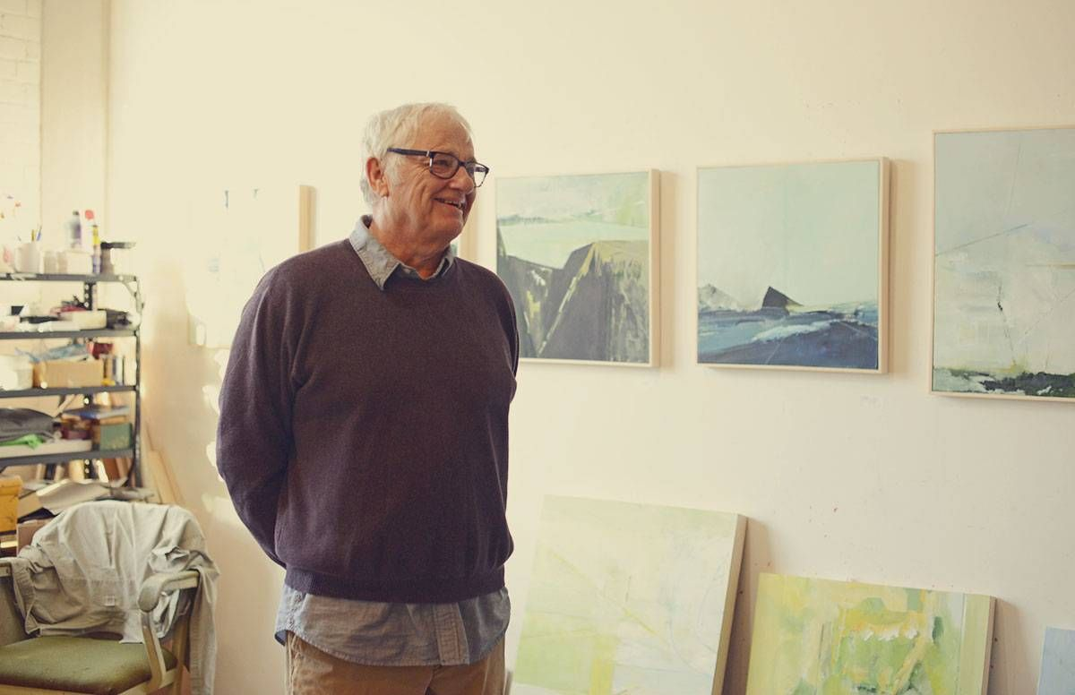 Artist James Wrayge poses near some of his paintings