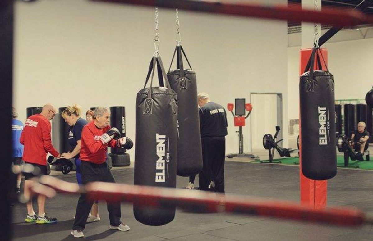 Student Jim Benson (foreground) practices different types of punches on a heavy bag while other students in the class work on other exercises.