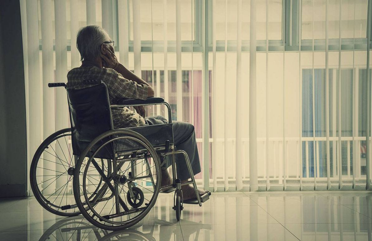 older man in a wheelchair, looking out a window