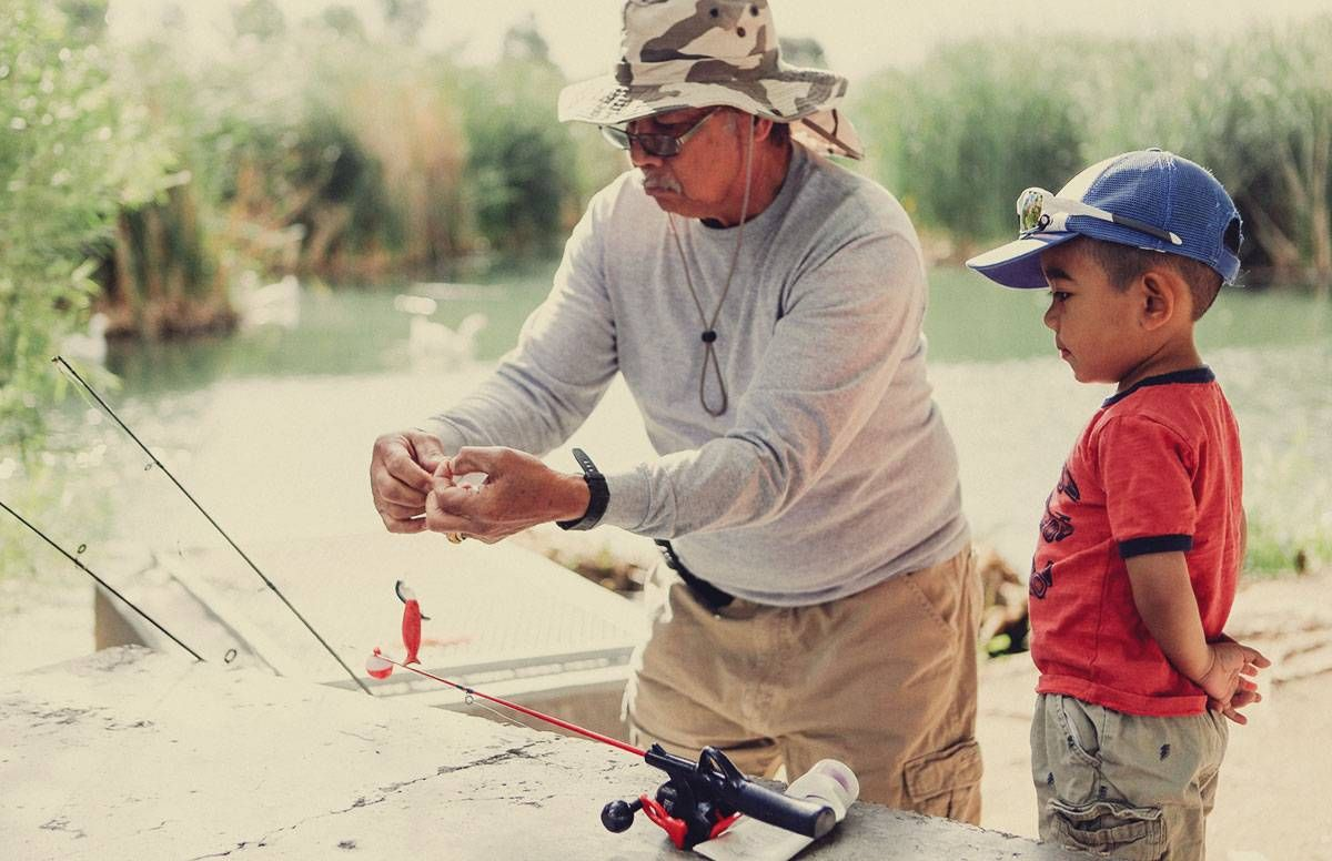 a grandfather helps his grandson bait a hook while they are fishing together
