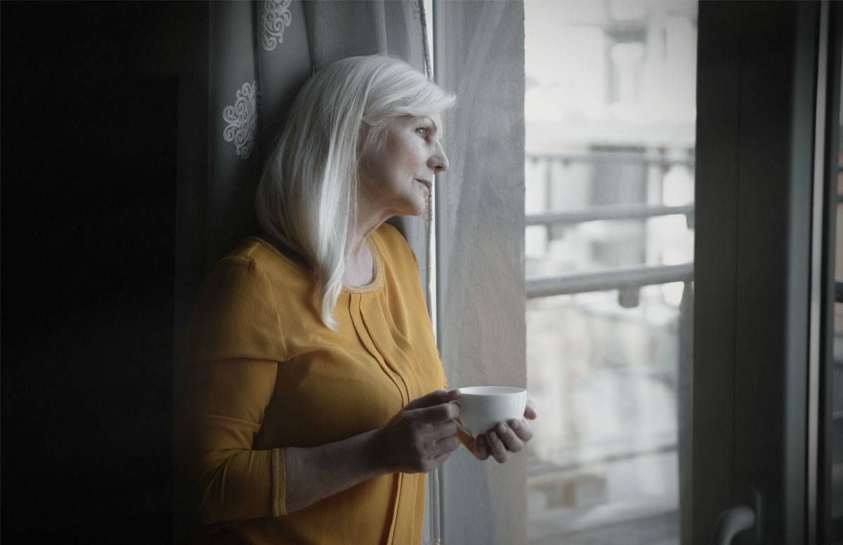 Woman looking wistfully out the window