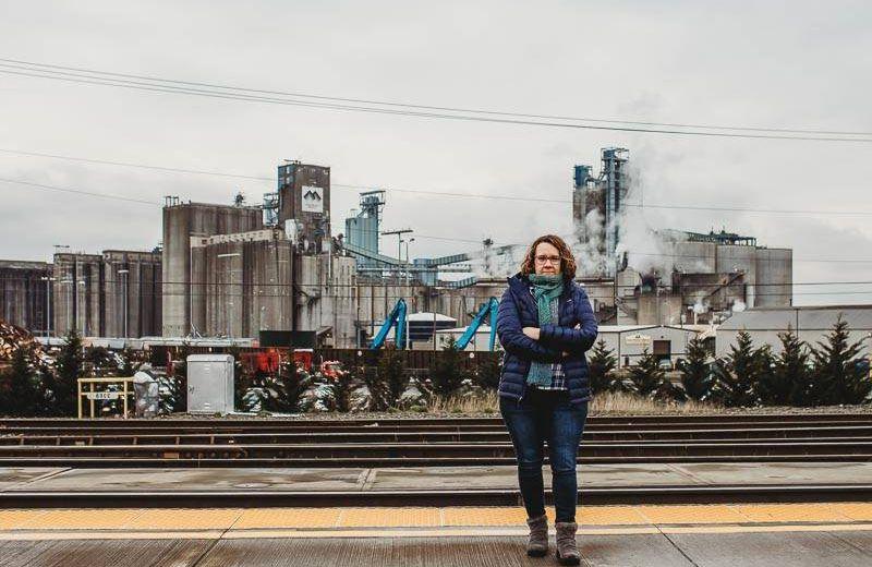 Linda Garcia standing in front of the Tesoro Savage Terminal at Port Washington.