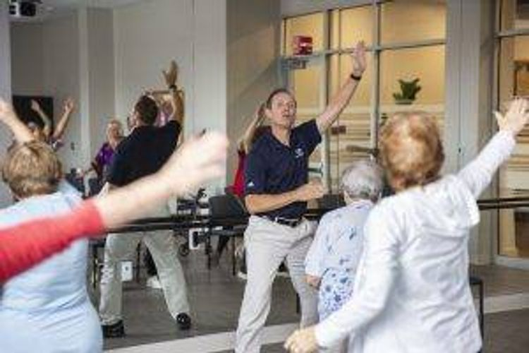 A man leads a group of older adults in an exercise class. They all have their arms raised and are moving with him.