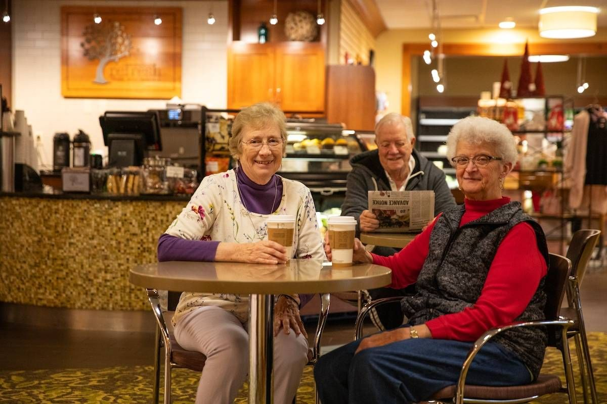 Two women and a man sit at a restaurant table with paper coffee cups. They are smiling at the camera.