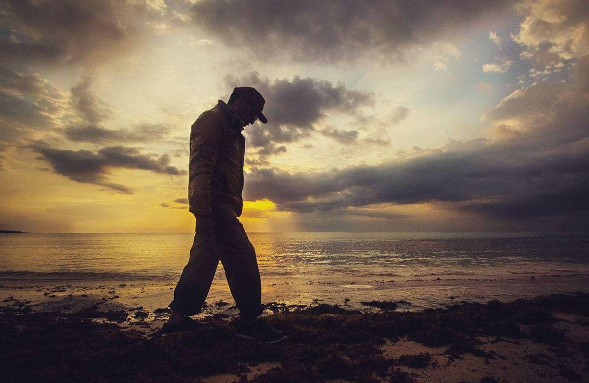 An older man walking alone alongside a body of water