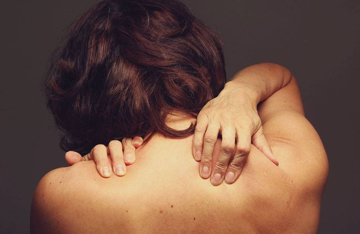 A woman with a naked back, touch her shoulders