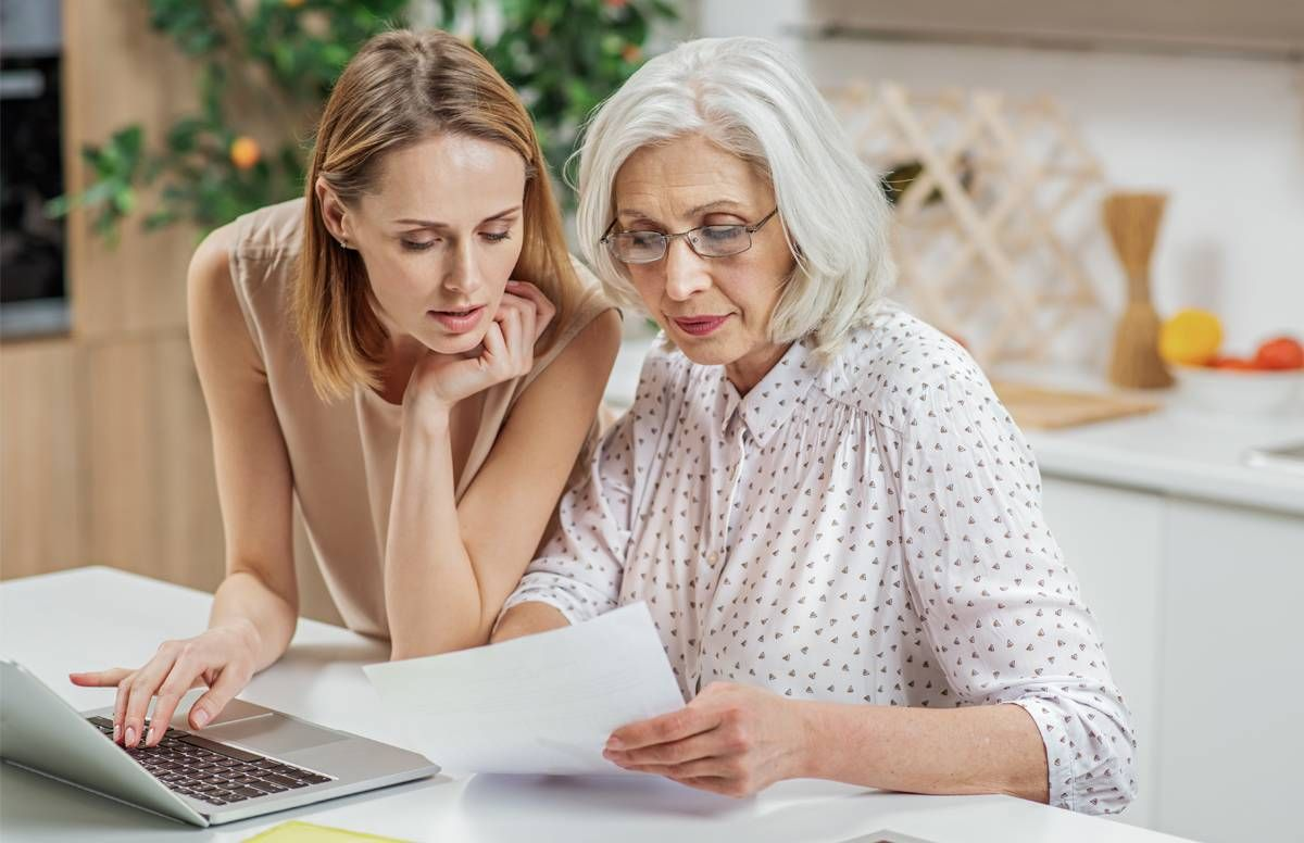 Mother with adult daughter, looking over documents