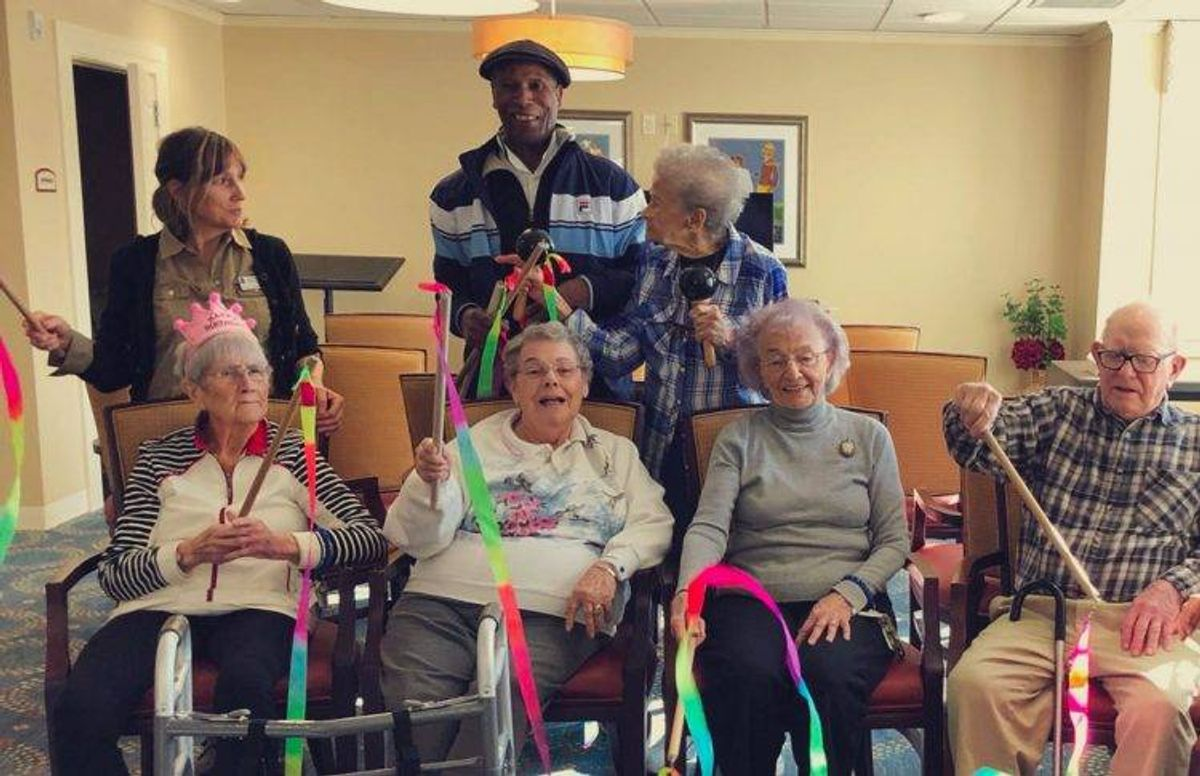 Art Carrington (standing in the middle) works with older adults at the Christopher Heights assisted living community in Northampton, Mass.