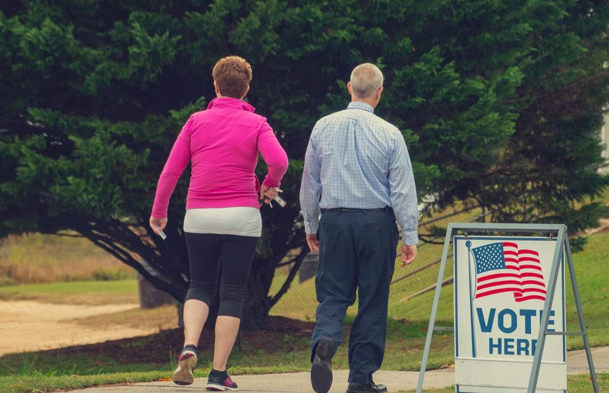 two middle-aged adults enter their polling place to vote