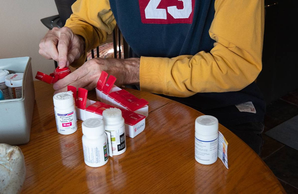 photo of long-term survivor of HIV/AIDS cutting pills and putting them in his pillbox